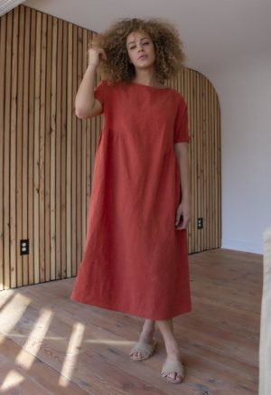 Back view of straight size model in Gathered Midi Dress in Papaya Linen