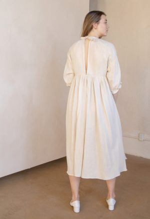 Back shot of straight size model in tan and white striped cotton Kacy Dress