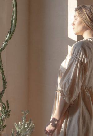 Close up shot of straight size model in tan and white striped cotton Kacy Dress
