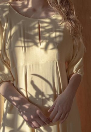 Close-up shot of straight sized model wearing the midi-length Tyler Dress in Italian Straw yellow.