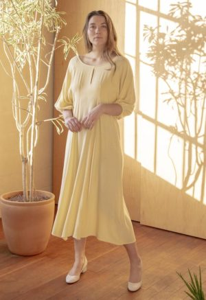 Font shot of straight sized model wearing the midi-length Tyler Dress in Italian Straw yellow.