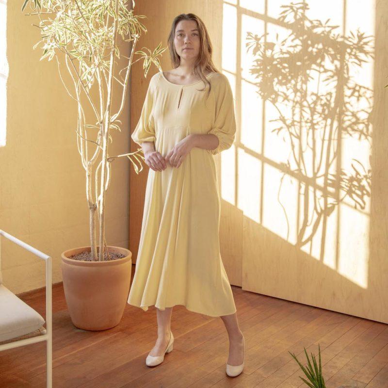Font shot of straight sized model wearing the midi-length Tyler Dress in Italian Straw yellow.