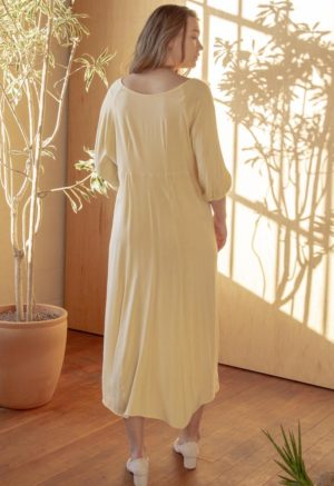 Back shot of straight sized model wearing the midi-length Tyler Dress in Italian Straw yellow.