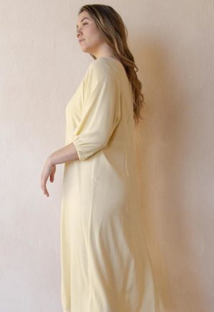 Side shot of straight sized model wearing the midi-length Tyler Dress in Italian Straw yellow.