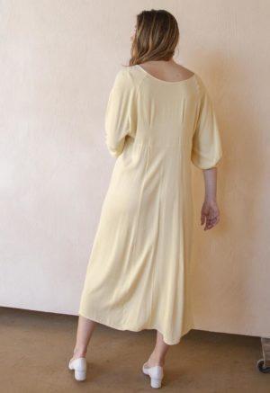 Back shot of straight sized model wearing the midi-length Tyler Dress in Italian Straw yellow.