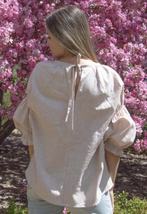 Back view of straight size model in Doja Blouse in Sandstone Stripe. Standing in front of lilac tree.