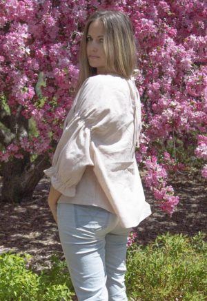 Side view of straight size model in Doja Blouse in Sandstone Stripe. Standing in front of lilac tree.