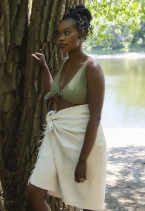 Straight size model standing against tree in Two-Way Top in Wild Sage Green and a white towel tied around her waist.
