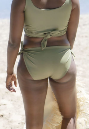 Back view of straight size model standing on beach in Tie Bikini Bottoms in Sage Green.