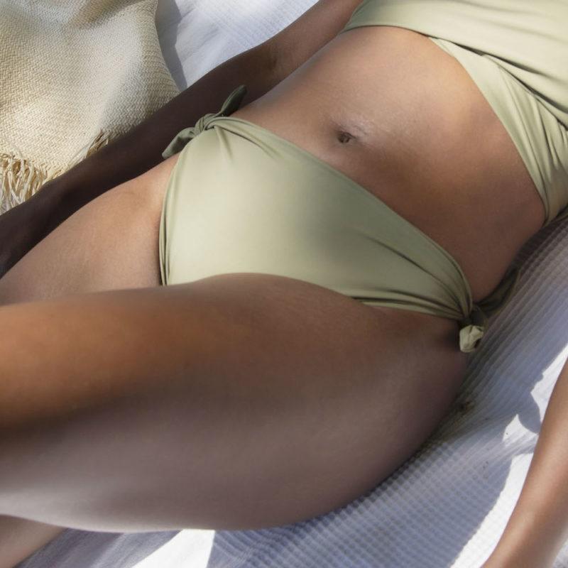Straight model laying on towel on beach in Tie Bikini Bottom in Wild Sage Green.