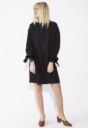 Front view of straight size model wearing Arm Tie Smock Dress in Black Lyocell.