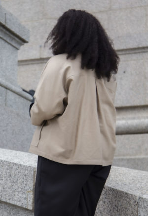 Back view of plus size model in Work Jacket in Nomad Hemp, unbuttoned.