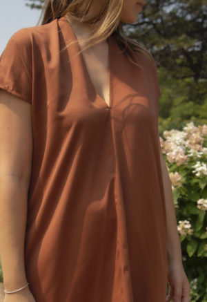 Close up front view of straight size model wearing Double V Kaftan in Copper Lyocell.