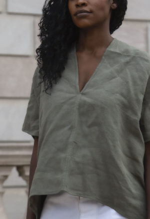 Front view of straight size model wearing Double V Top in Moss Linen.