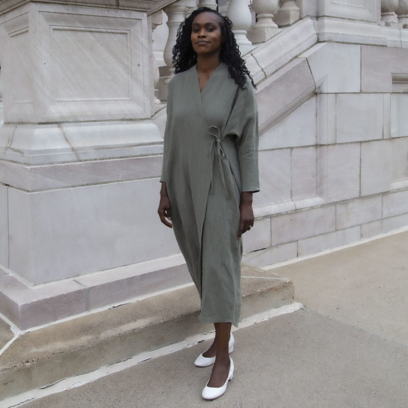 Front view of straight size model in Gathered Wrap Dress in Moss Linen.