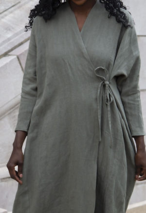 Close up front view of straight size model in Gathered Wrap Dress in Moss Linen.