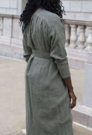 Back view of straight size model in Gathered Wrap Dress in Moss Linen.