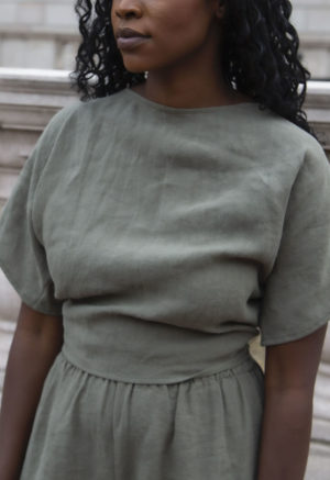Close up front view of straight size model wearing Short Sleeve Tie Top in Moss Linen.