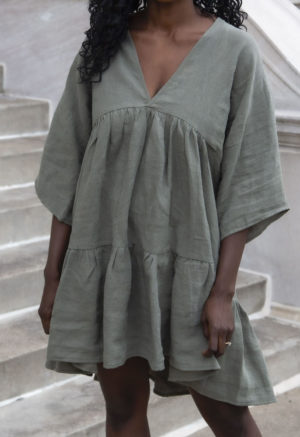 Front view of straight size model wearing Short Tiered Dress in Moss Linen.